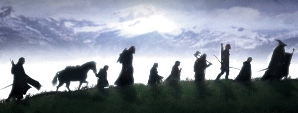 Nine walkers (the Fellowship of the Ring) silhouetted against a mountainous skyline
