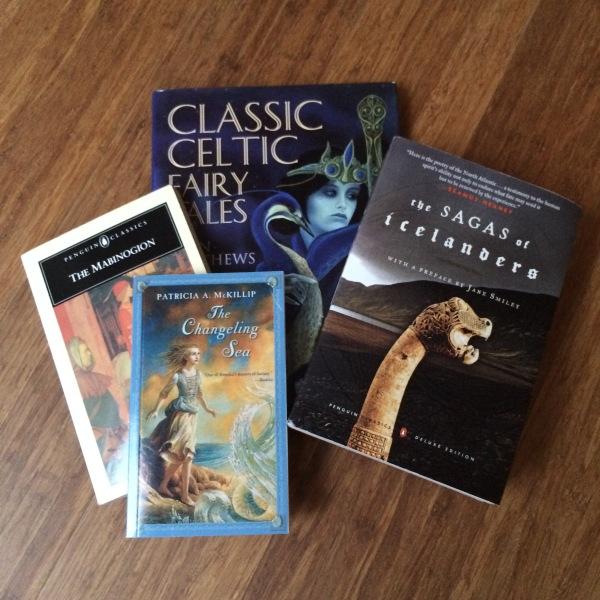 4 books of myths or fairy tales on a dark wood floor