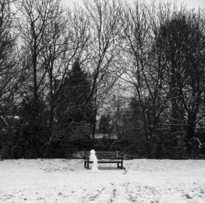 Snow person sat on a park bench, London 2013