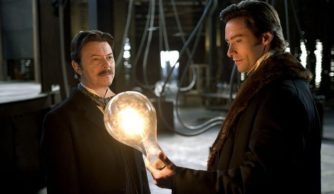 Hugh Jackman holding a huge lightbulb while David Bowie stares at him. Caption competitions were made for this but its a still from The Prestige