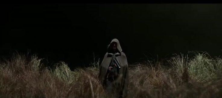A man in a daft big cloak in a field