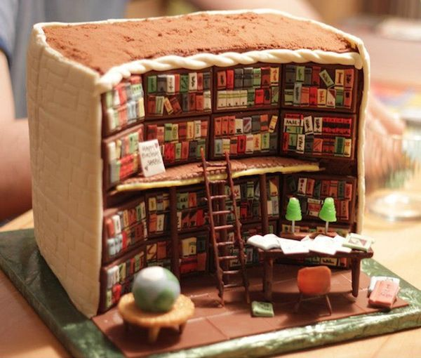 A cake that looks like a wall inside a library with shelves, books, book ladder and a desk full of books and reading lamps