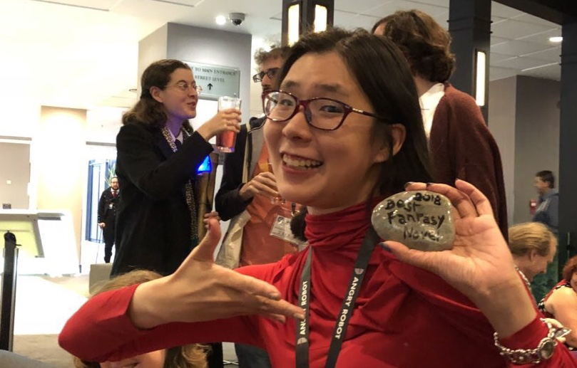 Jeannette Ng at Nine Worlds Geekfest 2018 holding a small rock that says Best Fantasy Novel 2018