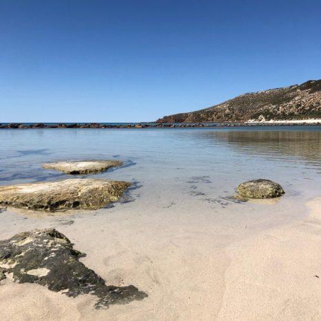 White sand and a calm lagoon under blue skies