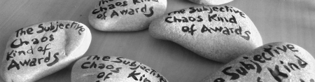Black and white photo of some pebbles, each painted with text: Subjective Chaos Kind of Awards