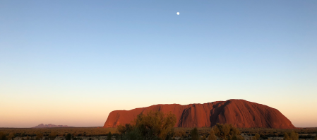Uluru glowing at dawn under a nearly-full moon, with Kata-Tjuta in the distance