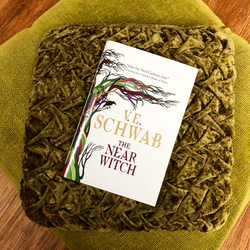 A copy of Titan Books hardcover rerelease of The Near Witch by V E Schwab lying on a pair of green cushions