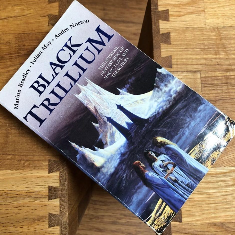 Book on a table: Black Trillium by Julian May, Andre Norton and Marion Zimmer Bradley