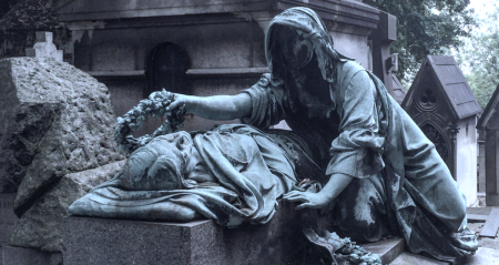 Detail from a Parisian tomb: a cloaked woman laying a wreath on the head of the dead